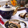 Tea and roll with poppy seeds — Stock Photo