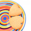Homemade heart shaped biscuits on varicoloured dish, isolated on white background. Christmas cookies — Stock Photo