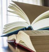 Livros sobre a mesa de madeira com luz de fundo janela — Foto Stock
