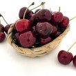 Cherries spilling out from the basket on white background — Stock Photo #12897779