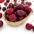 Cherries spilling out from the basket on white background - Stock Photo