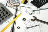 Calculator and measuring equipment with nuts on technical drawing — Stock Photo