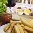 French fries and ketchup on kitchen table - Foto de Stock