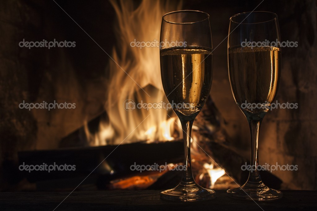 Glasses of champagne in front of fireplace  Stock Photo #16653353