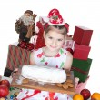 Pretty little girl in santa helper hat with gifts on white — Stock Photo #12856875