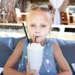 Little girl with ice cream milk shake at the cafe outdoors - Zdjęcie stockowe