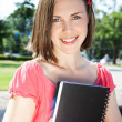 Beautiful student girl with notebook sitting outdoors — Stock Photo