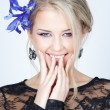 Beautiful blond girl with blue flowers — Stock Photo