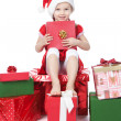 Pretty little girl in santa helper hat with gifts on white — Stock Photo #15823351