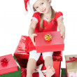 Pretty little girl in santa helper hat with gifts on white — Stock Photo #15823627