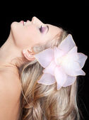 Young beautiful pretty woman with flower in long blonde hair — Stock Photo