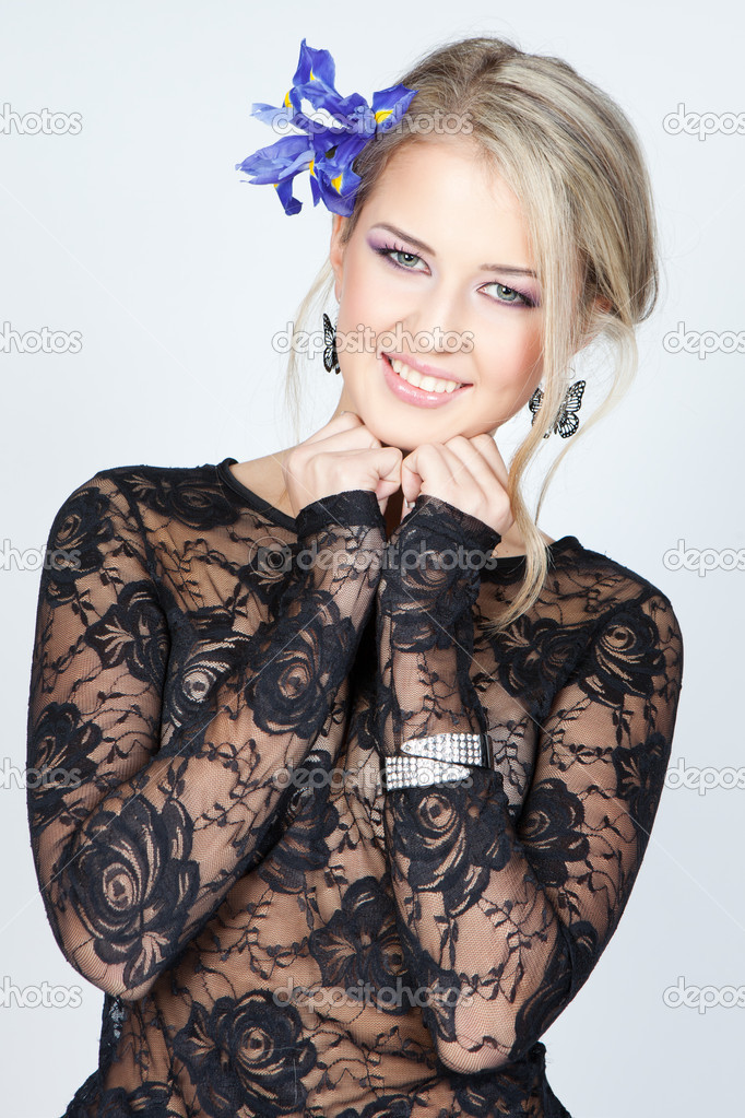 Picture of happy woman with blue flowers in hair over gray — Stock Photo #15822867