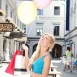 Young beautiful girl with shopping bags and balloons — Stock Photo
