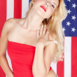 Beautiful blonde girl on the background of the American flag — Stock Photo