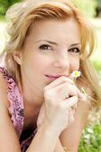 Güzel bir kadın çiçek ile çim üzerinde yalan — Stok fotoğraf