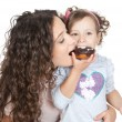 Picture of happy mother and little girl with chocolate donut - Stock Photo
