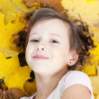Cute little smiling girl in autumn leaves — Stock Photo