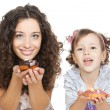 Picture of happy mother and little girl with colorful donuts - Stock Photo