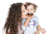Picture of happy mother and little girl with chocolate donut — Stock Photo