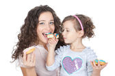Picture of happy mother and little girl with colorful donuts — Stock Photo