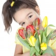 Beautiful little girl with a bouquet of tulips on white — Stock Photo