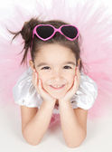 Beautiful little girl in a pink dress with glasses over white — Stock Photo