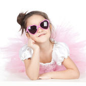 Beautiful little girl with glasses in a pink dress over white — Foto Stock