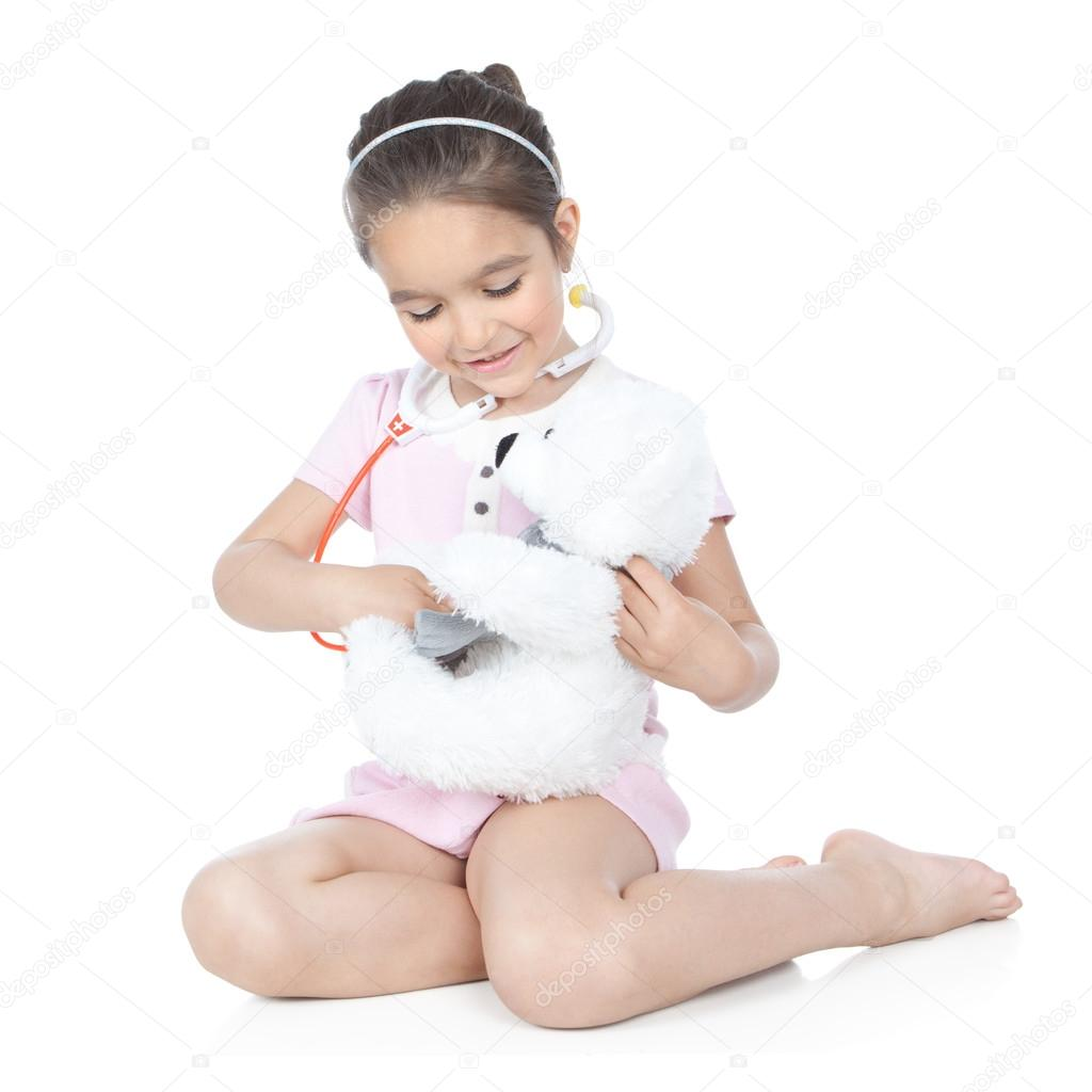 Smiling little girl playing doctor with stethoscope and white teddy bear over white background — Stock Photo #16021299