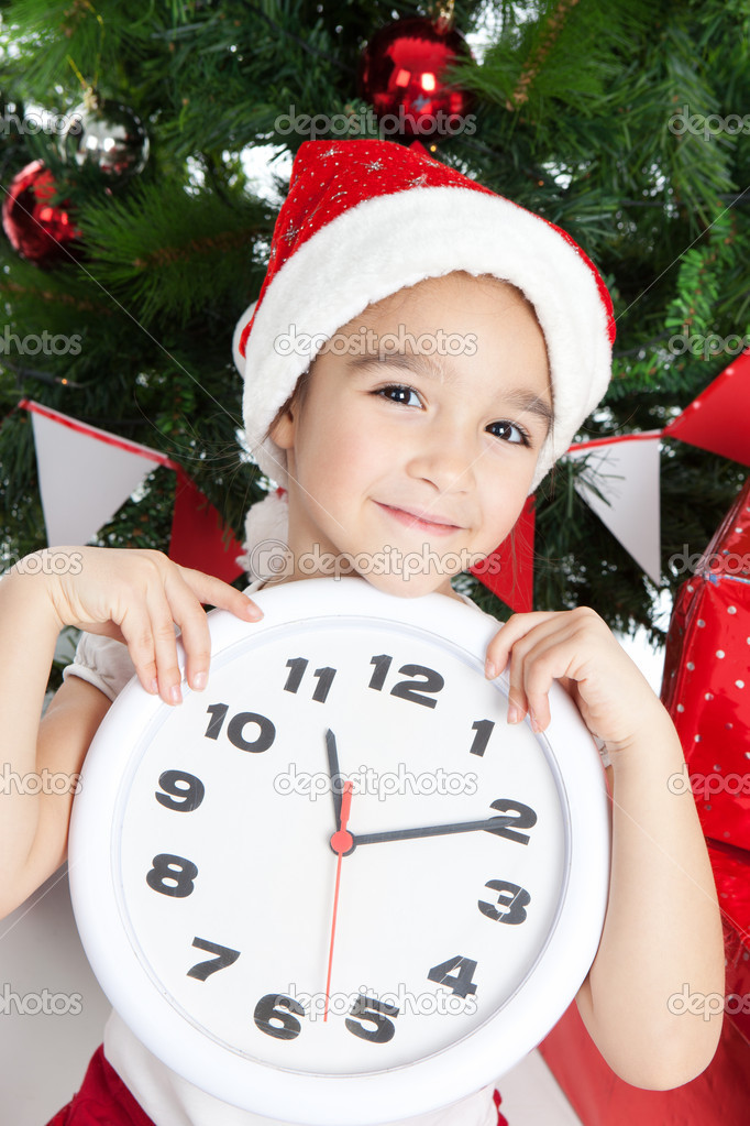 Happy small girl in Santa hat with big clock have a Christmas — Stock Photo #16021493