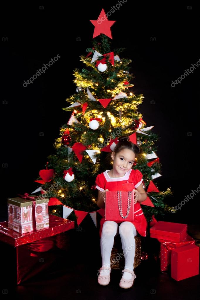 Little smilind girl with red gifts at Christmas night   Foto Stock #16021555