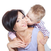 Closeup of cute little boy kissing beautiful mother over white — Stock Photo