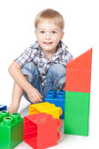 Portrait of emotionally kid plays with building blocks over whit — Stock Photo