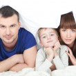 Happy family with child in bed - Stock Photo