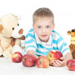 Little smiling boy eating apple on white — Stock Photo