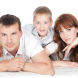 Smiling parents with little son lying on white background - Stock Photo