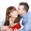 Happy young couple with red gift - Stock Photo