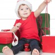 Pretty little girl in santa helper hat with gift over white — Stock Photo #18502081