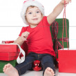 Pretty little girl in santa helper hat with gift over white - Stock Photo