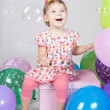 Little girl with balloons sitting on the gift  in studio - Stock Photo