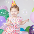 Little girl with balloons and soap bubbles in studio — Stock Photo