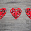 Three hearts on wooden background — Stock Photo