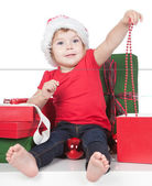 Pretty little girl in santa helper hat with gift over white — Stock Photo