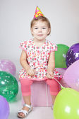 Little girl with balloons sitting on the gift in studio — Stock Photo