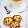Sweet cakes with cup of tea on white table — Stock Photo
