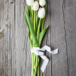 Постер, плакат: Bouquet of white tulips on wooden table