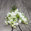 Lilies of the valley on wooden background — Stock Photo