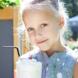 Stock Photo: Little girl with ice cream milk shake outdoor