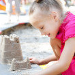 Little happy girl building a sand castle in the sandbox — Stock Photo