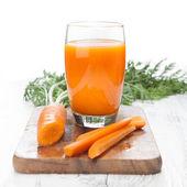Carrot juice with fresh carrots on white table — Stock Photo