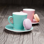 Coffee cups with french macaroons on table — Stock Photo